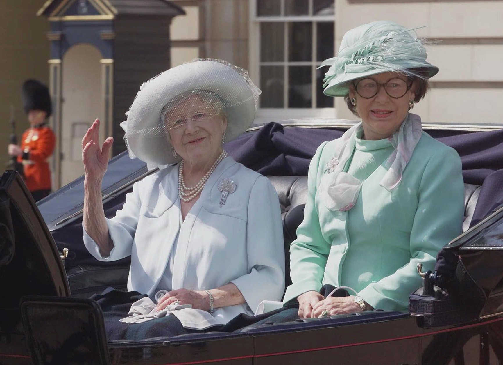 Britain's Queen Mother, left, and her youngest daughter Princess Margaret, sit in an open top horse drawn carriage as they leave Buckingham Palace, in central London, for the short ride to Horse Guards parade, where senior members of the Royal family gather for the annual Trooping the Colour ceremony, Saturday, June 17, 2000.  Queen Elizabeth II will take the salute at the military parade on London's Horse Guards, marking the sovereign's official birthday. (AP Photo/Alban Donohoe, Pool)