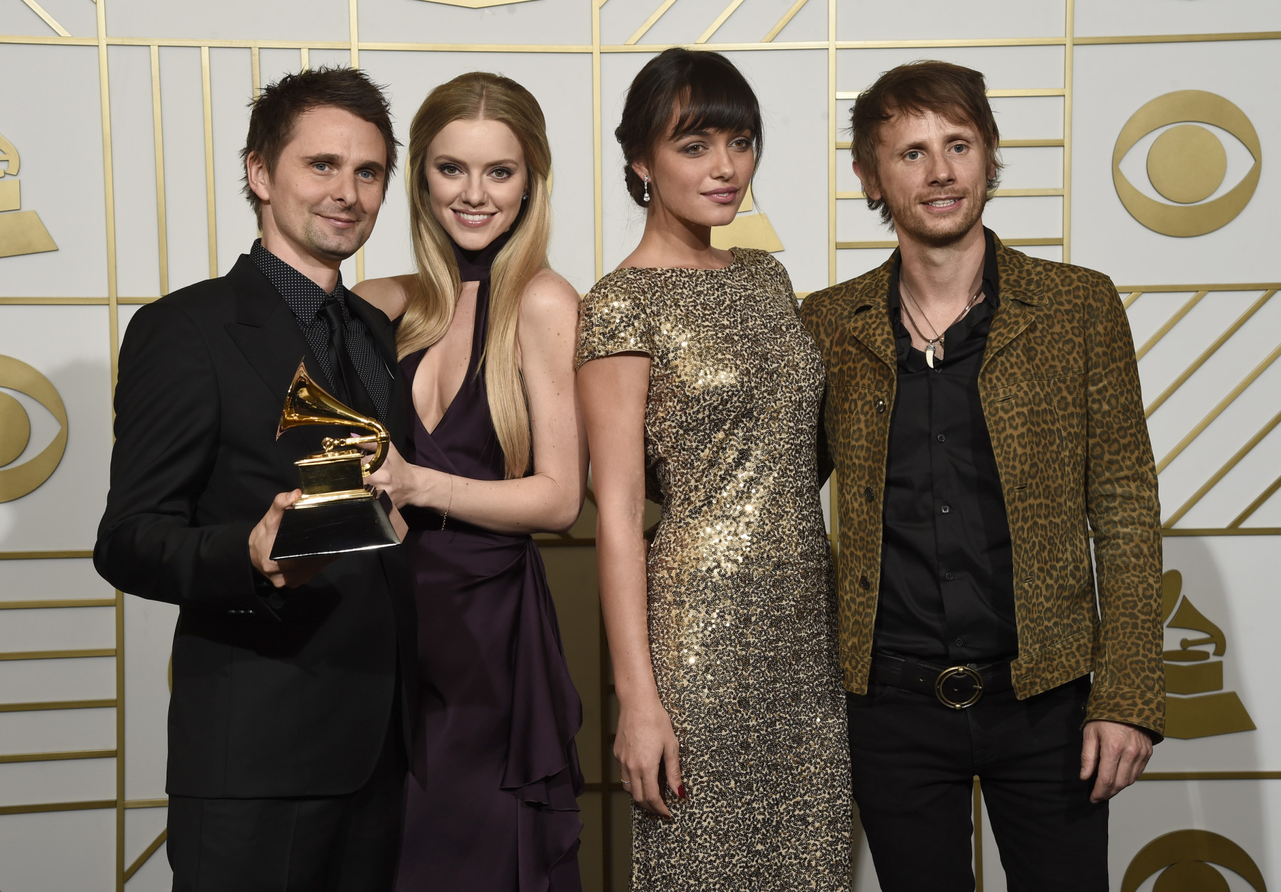 "Matt Bellamy, left, and Dominic Howard, right of Muse pose in the press room with the award for best rock album for ""Drones"" along with Elle Evans, second left and Rayana Ragan, second right at the 58th annual Grammy Awards at the Staples Center on Monday, Feb. 15, 2016, in Los Angeles. (Photo by Chris Pizzello/Invision/AP)"
