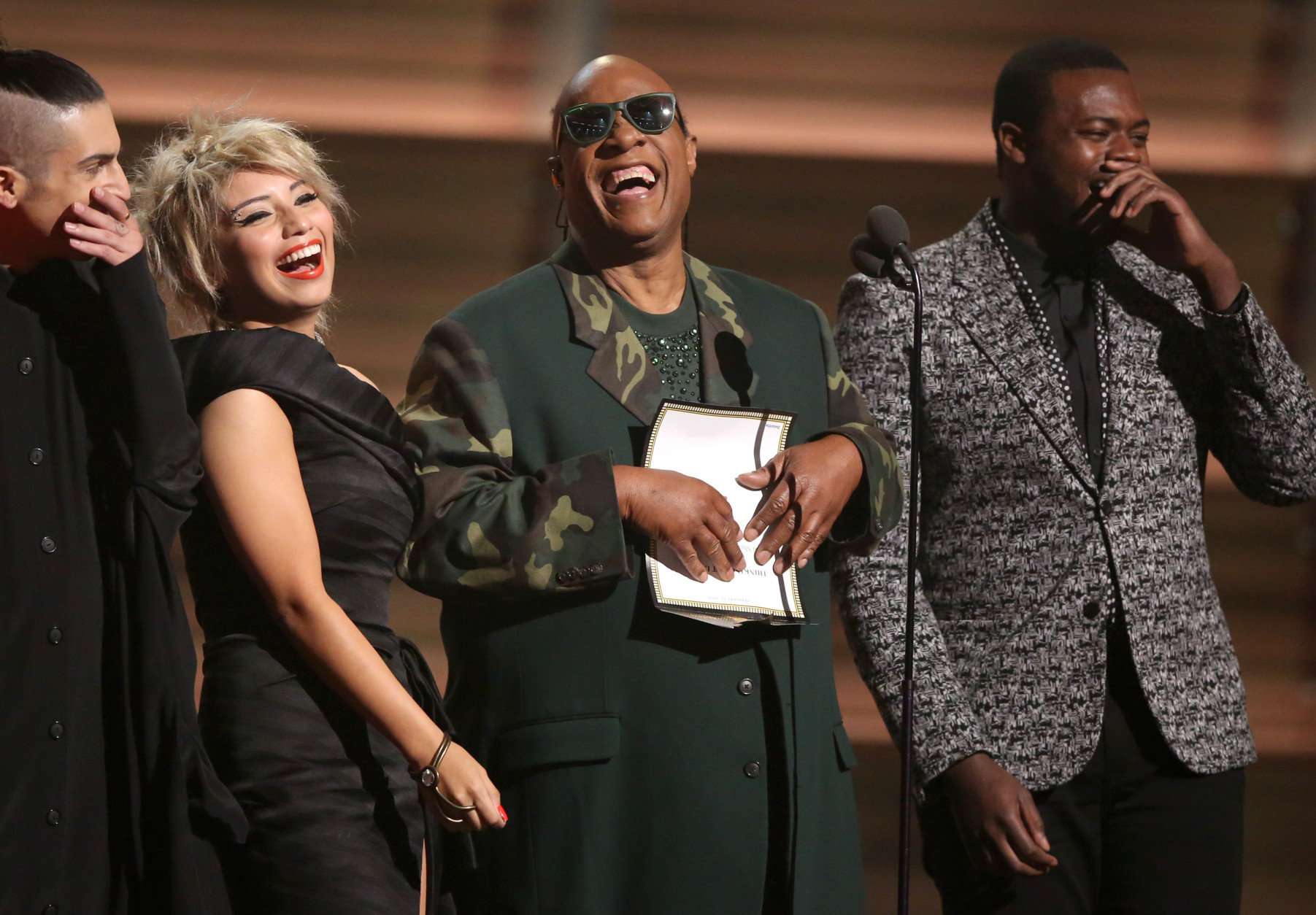 Stevie Wonder, center, and from left Mitch Grassing, Kristin Maldonado, and Kevin Olusola of Pentatonix present the award for song of the year at the 58th annual Grammy Awards on Monday, Feb. 15, 2016, in Los Angeles. (Photo by Matt Sayles/Invision/AP)