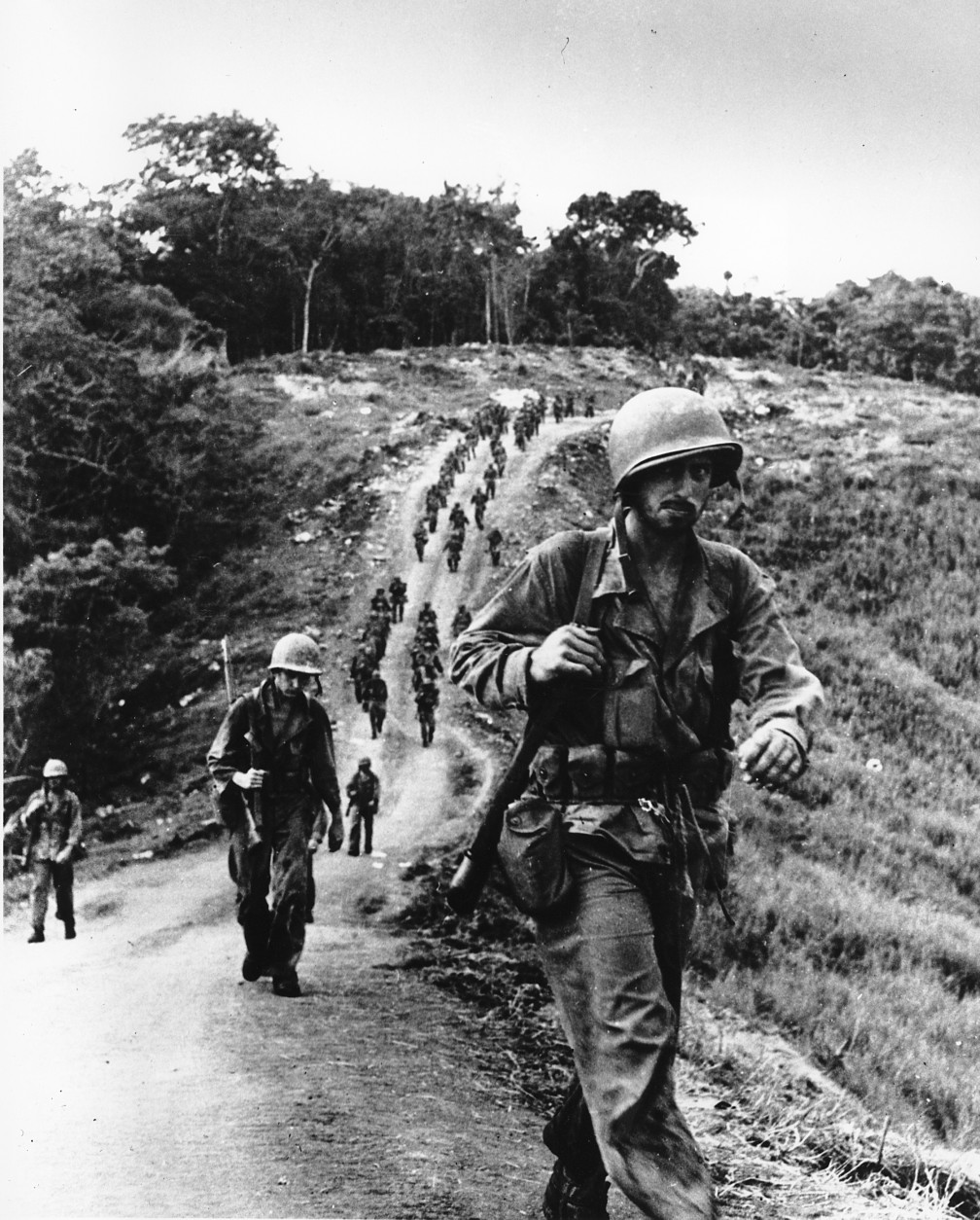 U.S. soldiers, bearded and weary, plod along a road toward an American Base of Operations in Guadalcanal, Solomon Islands in Feb. 1943. They have been relieved after a 21-day period of fighting the Japanese in World War II. (AP Photo)