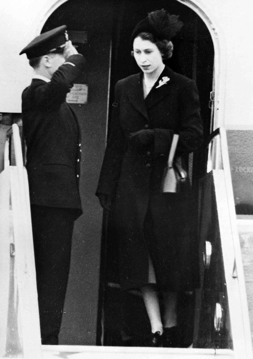 Britain's Queen Elizabeth II steps from her plane, for the first time as sovereign, at London Airport, on Feb. 7, 1952, after cutting short her official trip to Kenya on the death of her father King George VI.  (AP Photo)