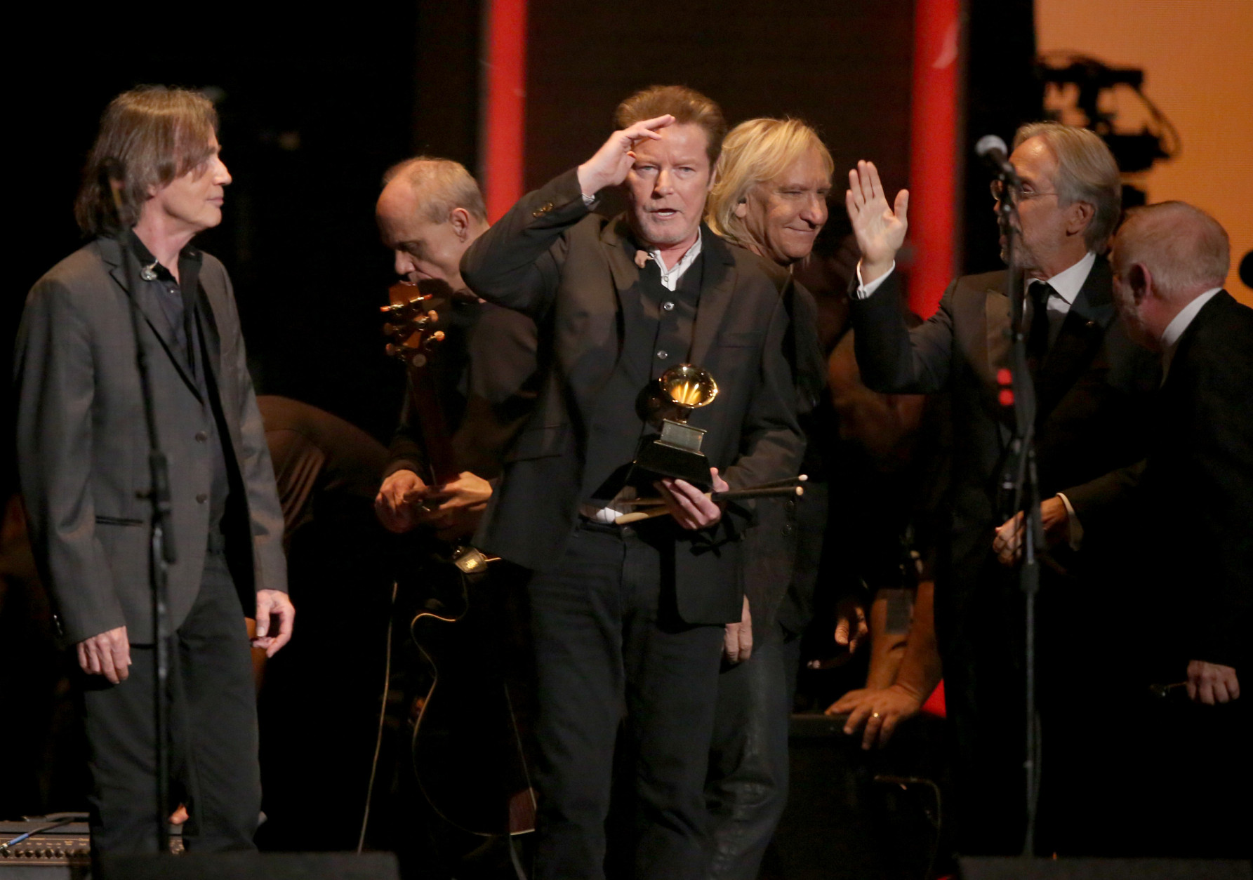 "Don Henley, center, holds The Eagles' 1978 Grammy award for record of the year for ""Hotel California"" at the 58th annual Grammy Awards on Monday, Feb. 15, 2016, in Los Angeles. (Photo by Matt Sayles/Invision/AP)"