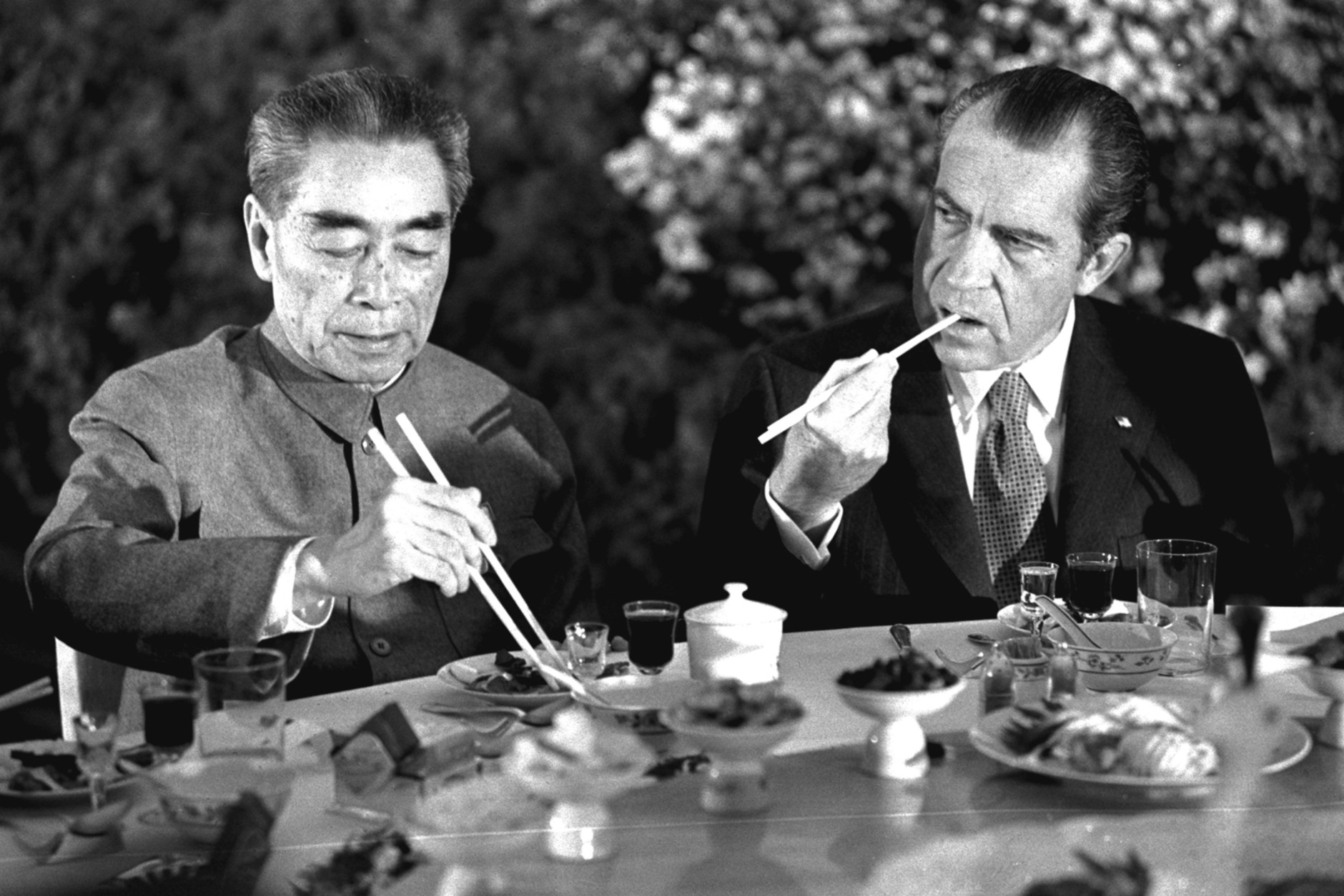 Premier Chou En-lai bends over in the Chinese manner to eat with chopsticks as President Nixon watches at a banquet in Shanghai, February 28, 1972.  (AP Photo/stf)