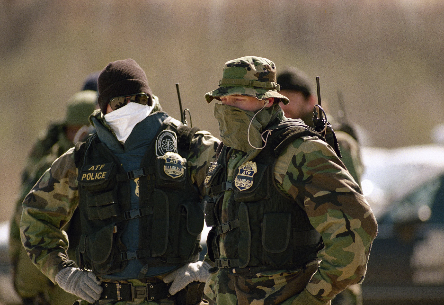 Two Alcohol, Tobacco and Firearms agents cover their faces to guard against the cold as a major cold front moved through central Texas on Saturday, March 13, 1993. They are guarding the Branch Davidian compound as the standoff with the religious cult enters its 14th day. (AP Photo/David Longstreath)