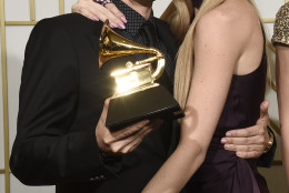 "Matt Bellamy, left, of Muse poses in the press room with the award for best rock album for ""Drones"", and Elle Evans at the 58th annual Grammy Awards at the Staples Center on Monday, Feb. 15, 2016, in Los Angeles. (Photo by Chris Pizzello/Invision/AP)"