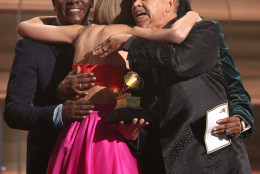 "Philip Bailey, from left, Verdine White, obscured, and Ralph Johnson of Earth Wind & Fire present Taylor Swift the award for album of the year for ""1989"" at the 58th annual Grammy Awards on Monday, Feb. 15, 2016, in Los Angeles. (Photo by Matt Sayles/Invision/AP)"