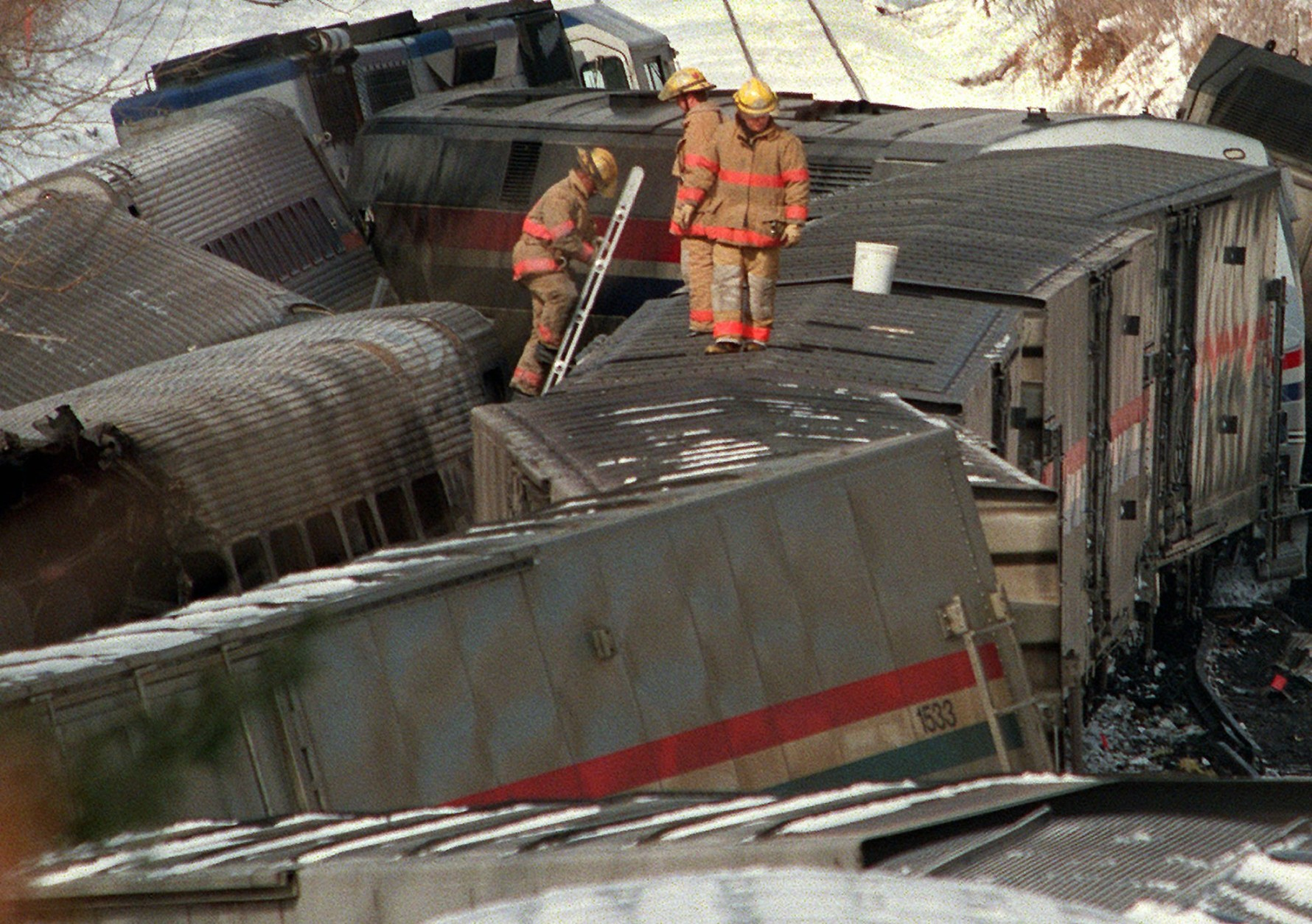 Firemen climb through the wreckage of the burned MARC commuter train in Silver Spring, Md. Saturday Feb. 17, 1996 that was hit by  an Amtrak train  Friday evening. At least 11 passengers on the commuter train were killed.   (AP Photo/Ruth Fremson)