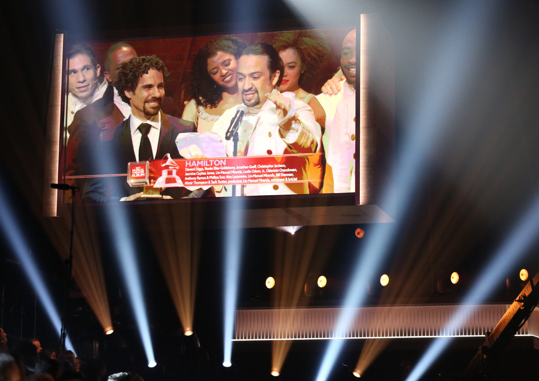 "Lin-Manuel Miranda, right, appears on screen accepting the award for best musical theater album for ""Hamilton"" at the 58th annual Grammy Awards on Monday, Feb. 15, 2016, in Los Angeles. (Photo by Matt Sayles/Invision/AP)"