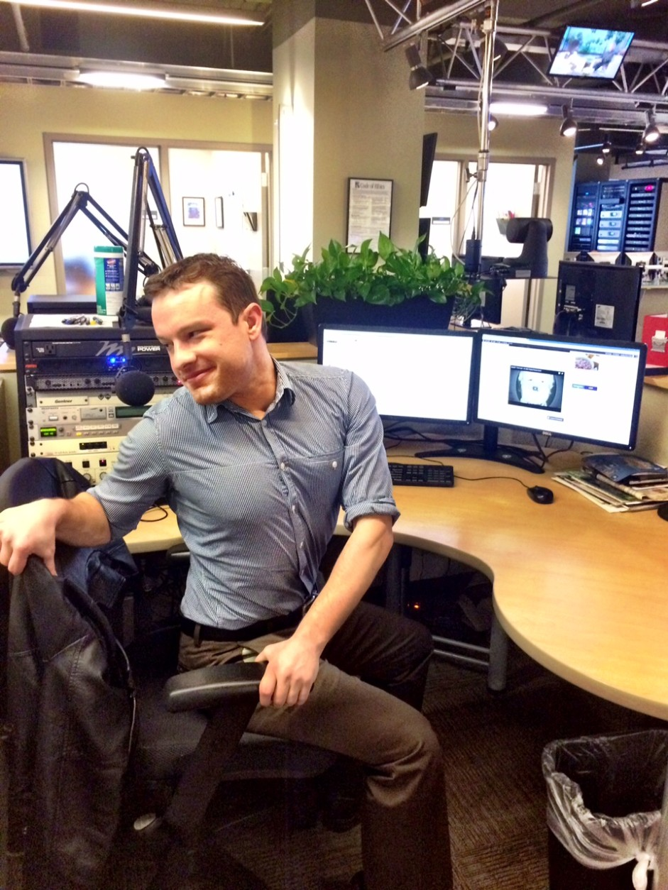 WTOP Entertainment Editor Jason Fraley takes a break from interviewing celebrities to do a seated twist at work. (WTOP/Rachel Nania)