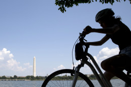 A girl on a bicycle pedals around the Tidal Basin with the Washington Monument in the background in Washington Monday, Aug. 17, 2015. (AP Photo/Carolyn Kaster)