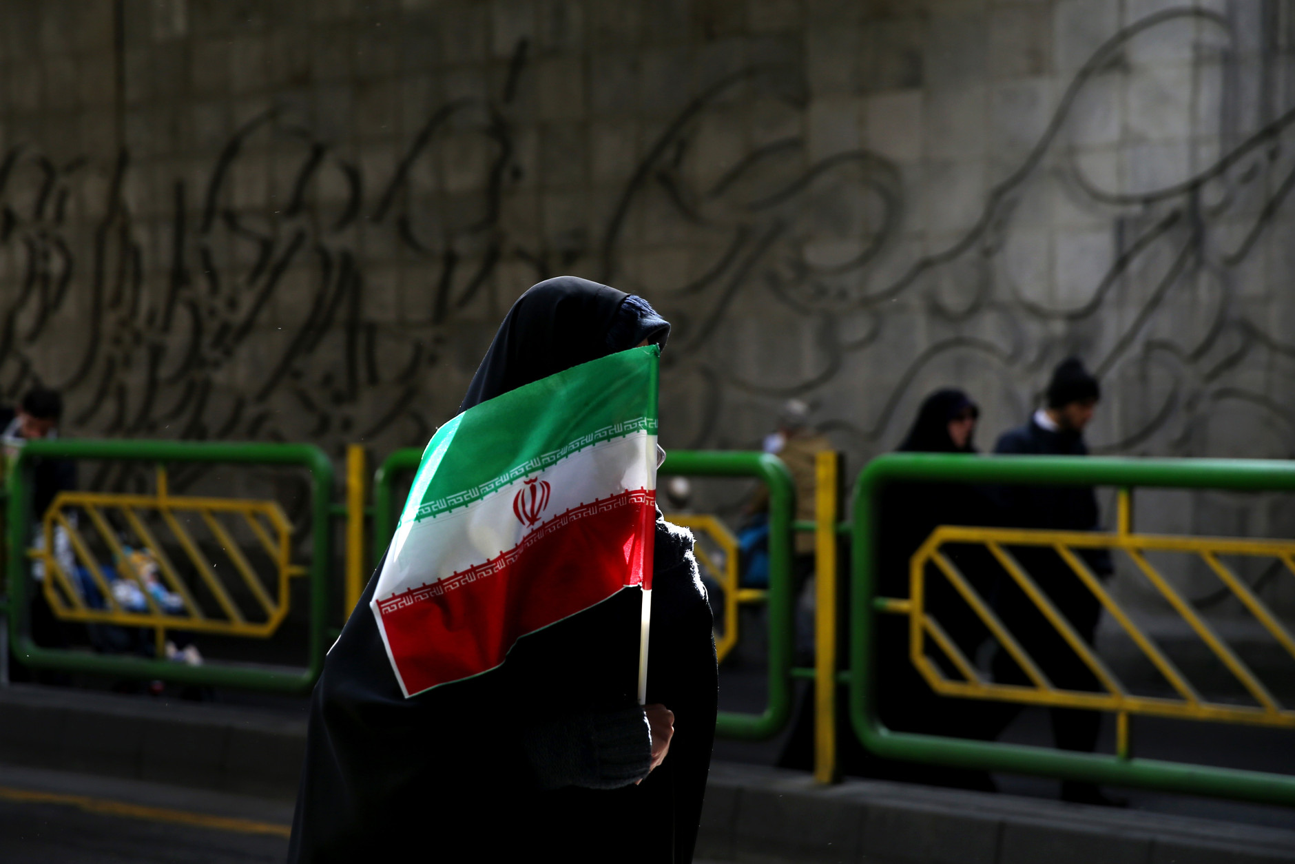 FILE - In this Thursday, Feb. 11, 2016 file photo, an Iranian woman holds the national flag during a rally commemorating the 37th anniversary of the Islamic revolution, in Tehran, Iran. The nationwide rallies commemorate Feb. 11, 1979, when followers of Ayatollah Khomeini ousted U.S.-backed Shah Mohammad Reza Pahlavi. (AP Photo/Ebrahim Noroozi)