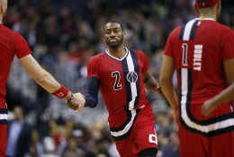 Washington Wizards guard John Wall (2) celebrates a play with Washington Wizards center Marcin Gortat, left, from Poland,in the second half of an NBA basketball game against the Boston Celtics, Saturday, Jan. 16, 2016, in Washington. The Celtics won 119-117. (AP Photo/Alex Brandon)