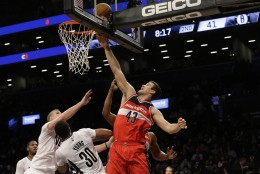 Washington Wizards forward Kris Humphries (43) goes to the basket past Brooklyn Nets forward Thaddeus Young (30) and center Mason Plumlee during the first half of an NBA basketball game, Friday, April 10, 2015, at  New York.  (AP Photo/Mary Altaffer)