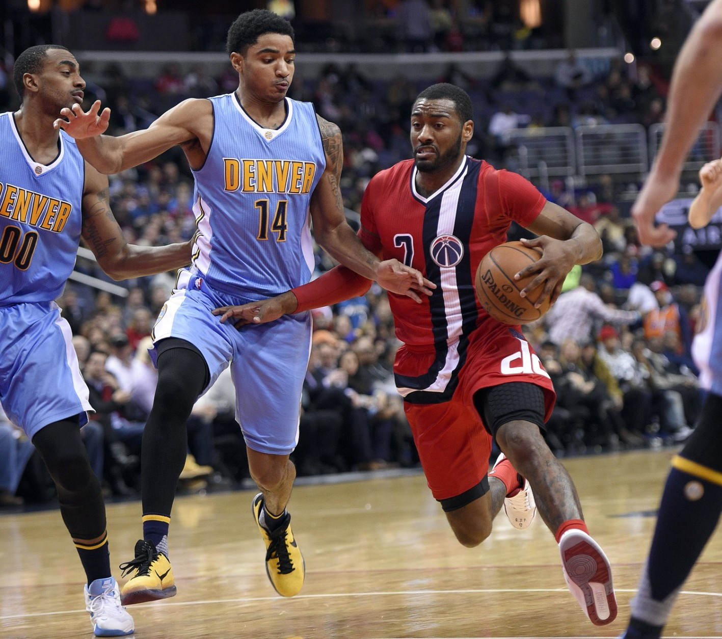 Washington Wizards guard John Wall (2) drives to the basket against Denver Nuggets guard Gary Harris (14) and forward Darrell Arthur (00) during the second half of an NBA basketball game, Thursday, Jan. 28, 2016, in Washington. The Nuggets won 117-113. (AP Photo/Nick Wass)