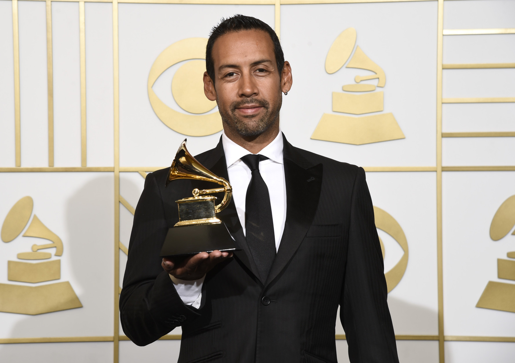 "Antonio Sanchez poses in the press room with the award for best score soundtrack for visual media for ""Birdman"" at the 58th annual Grammy Awards at the Staples Center on Monday, Feb. 15, 2016, in Los Angeles. (Photo by Chris Pizzello/Invision/AP)"