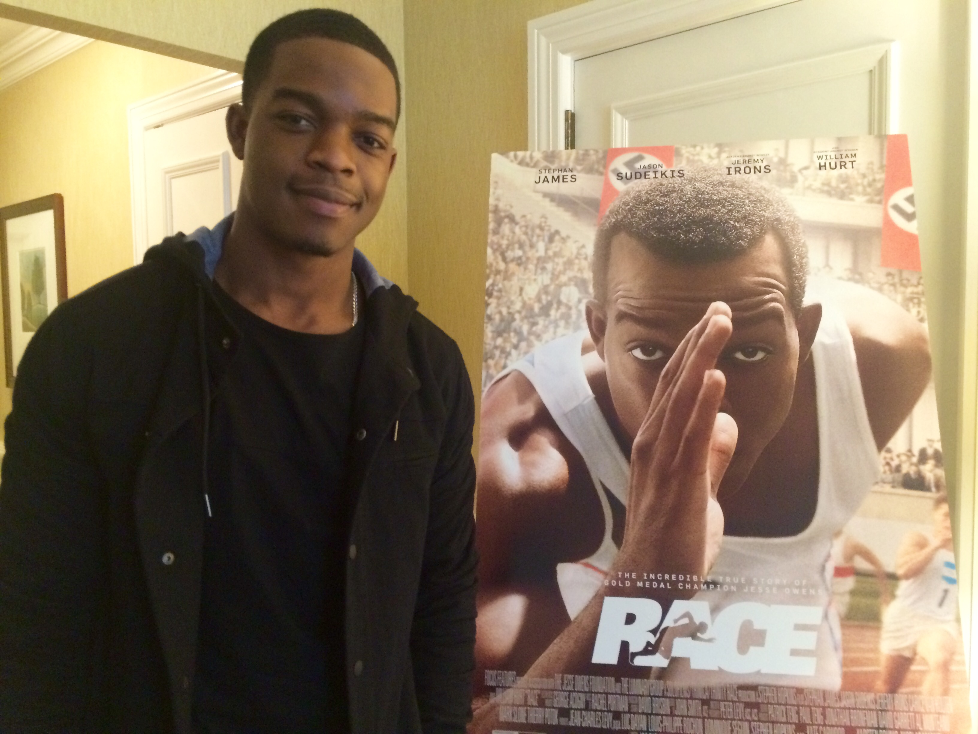 "Actor Stephan James poses next to a poster of ""Race"" during a visit to Dupont Circle in D.C. (WTOP/Jason Fraley)"