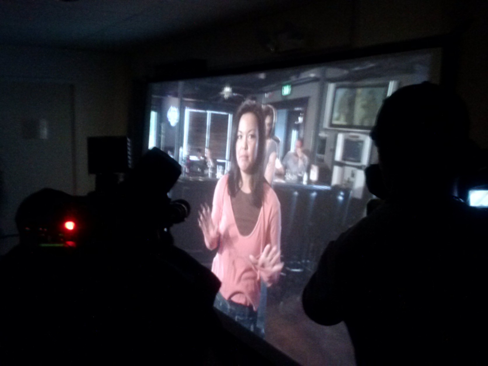 A woman holds her hands up on screen in a training simulation. Officers can point simulated weapons at the subject on screen if they do not cooperate with officers. (WTOP/Max Smith)
