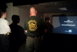 A trainer explains to officers how the simulator works. (WTOP/Max Smith)