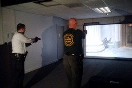 Officers point simulated weapons at the target shown on screen during a de-escalation simulation. (WTOP/Max Smith)