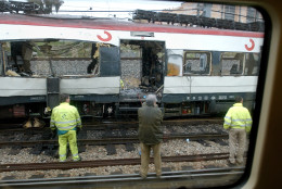 Workers stand next to a bomb damaged passenger train a day after a number of explosions  in Madrid, in this March 12, 2004, file photo. A Spanish judge on Tuesday, April 11, 2006, handed down the first indictments in the Madrid train bombings of 2004, charging 29 people with murder, terrorism or other crimes after a two-year probe. (AP Photo/Peter DeJong)