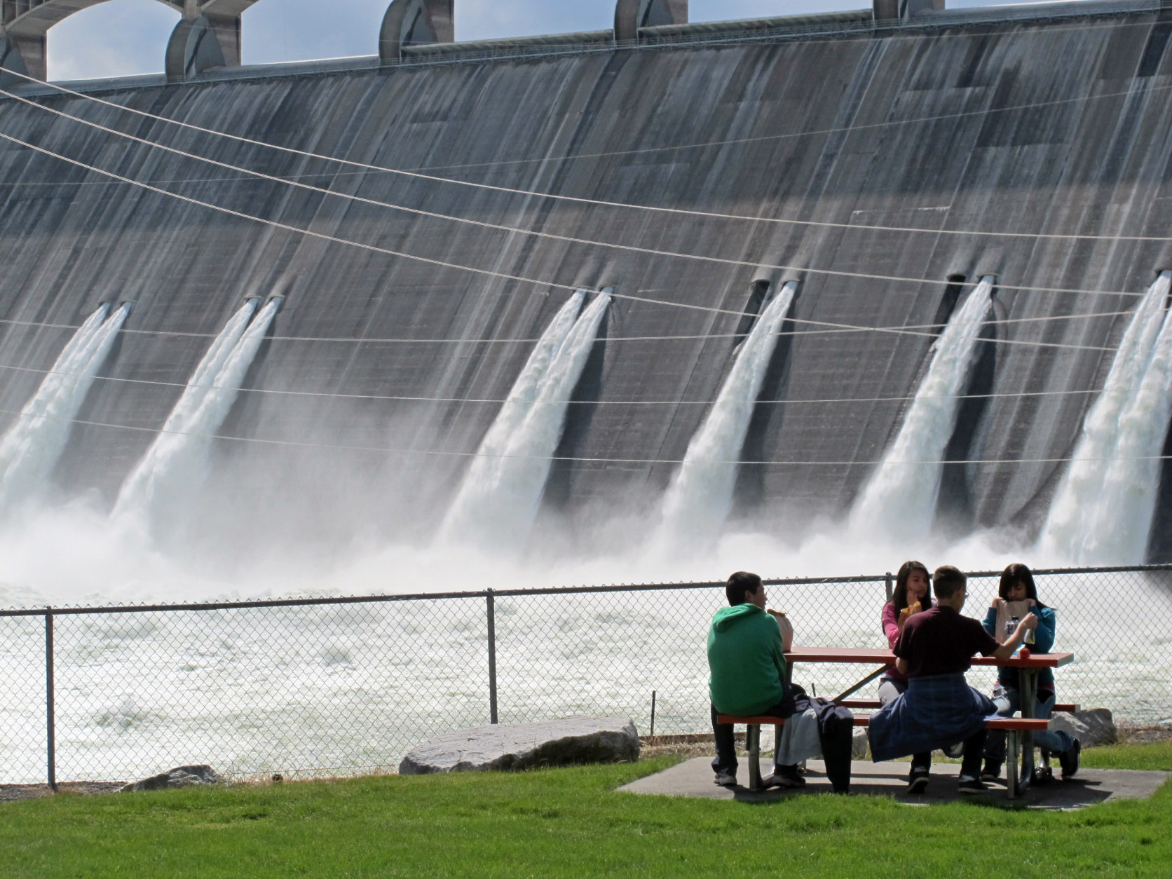 FILE - In this June 1, 2011 file photo, students on a field trip eat lunch as water is released from Grand Coulee Dam, Wash. The Grand Coulee Dam, a product of the Great Depression, is getting a major facelift as federal operators seek to squeeze even more power out of the nation's largest hydroelectric dam. (AP Photo/Nicholas K. Geranios)