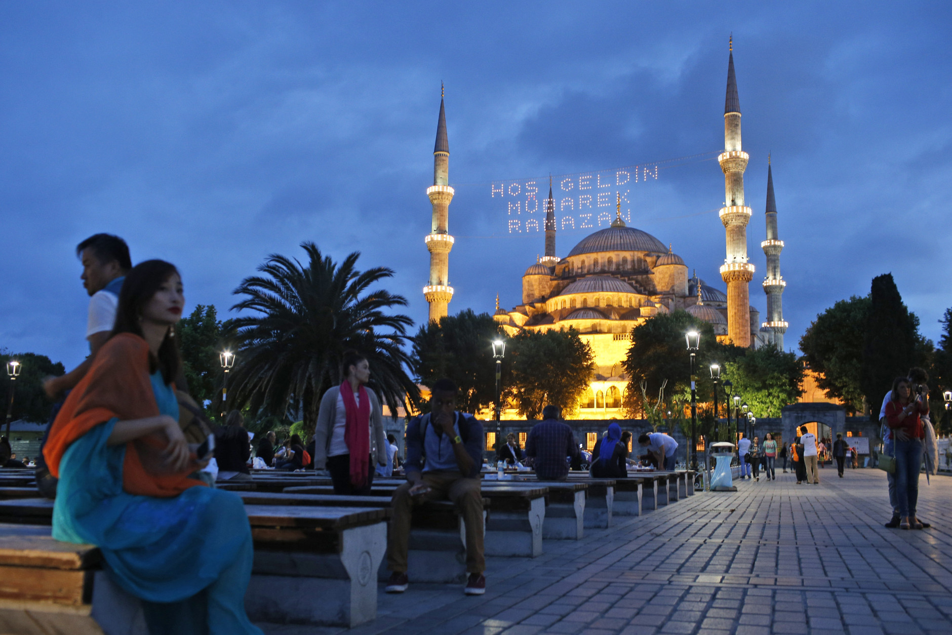 People gather backdroped by the the iconic Sultan Ahmed Mosque, better known as the Blue Mosque, decorated with lights marking the month of Ramadan, in the historic Sultanahmet district of Istanbul, Turkey, Thursday, June 18, 2015. The lights read in Turkish: 'Welcome Holy Ramadan'.  Muslims throughout the world are marking Ramadan - a month of fasting during which the observants abstain from food, drink and other pleasures from sunrise to sunset. After an obligatory sunset prayer, a large feast known as 'iftar' is shared with family and friends. (AP Photo/Emrah Gurel)