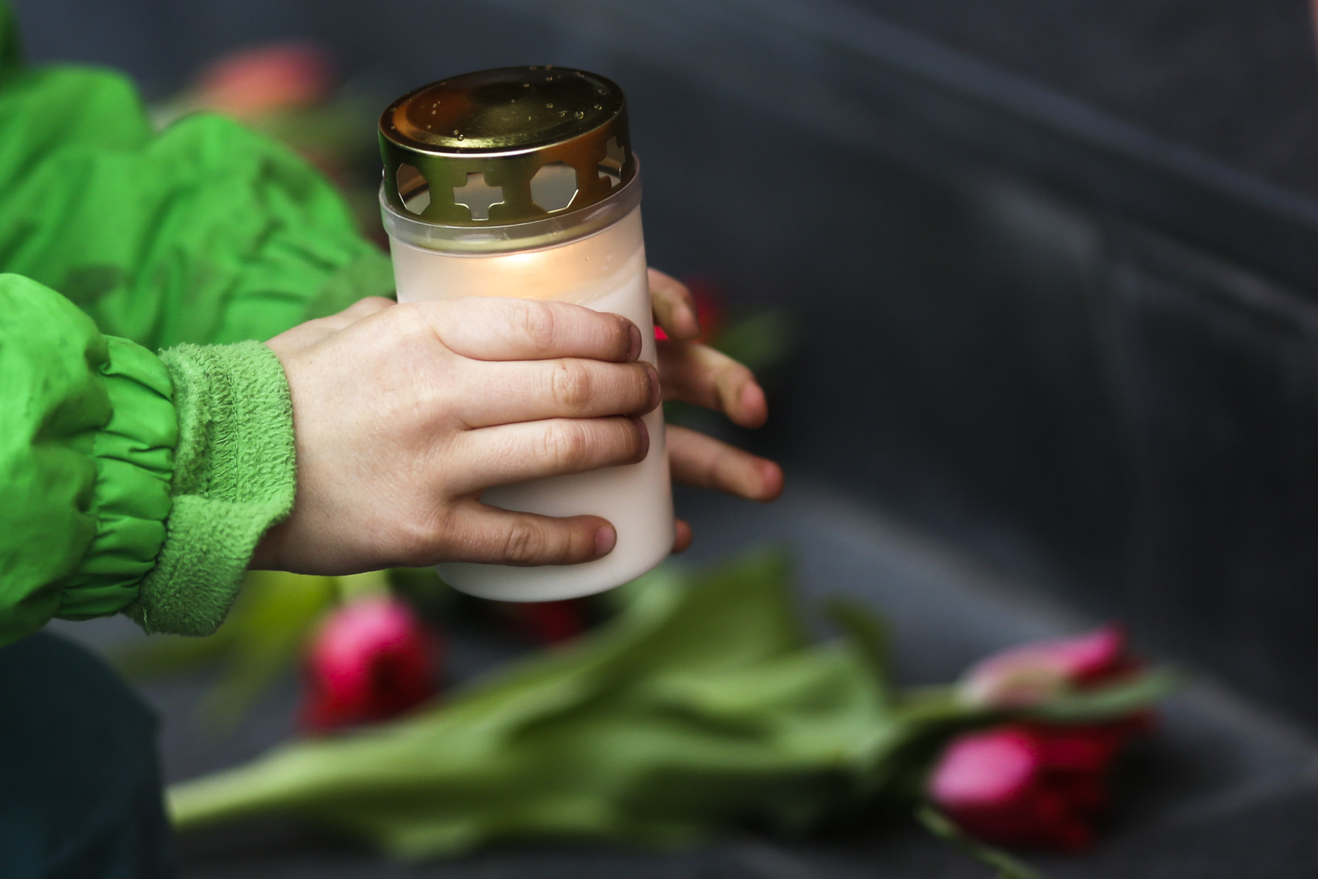 After deadly attacks on the Brussels airport and its subway system, a boy places a candle in front of the Belgian  Embassy in Berlin, Germany, Tuesday, March 22, 2016. (AP Photo/Markus Schreiber)