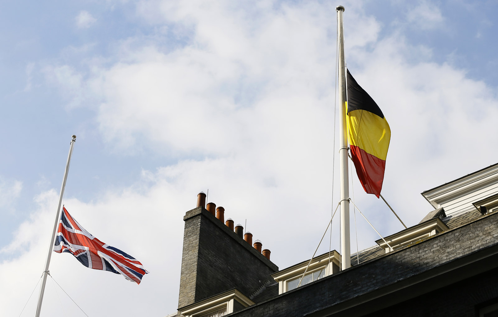 The Belgium and British flag fly at half staff above Downing Street in London, following the attacks in Brussels, Tuesday, March, 22, 2016. Authorities in Europe and beyond have tightened security at airports, on subways, at the borders and on city streets after deadly attacks Tuesday on the Brussels airport and its subway system. (AP Photo/Kirsty Wigglesworth)