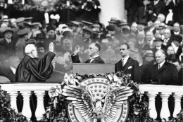 President Franklin D. Roosevelt takes the oath of office from Chief Justice Charles E. Hughes at the inauguration, March 4, 1933. At right is Herbert Hoover and behind the president is his eldest son James Roosevelt. (AP Photo)