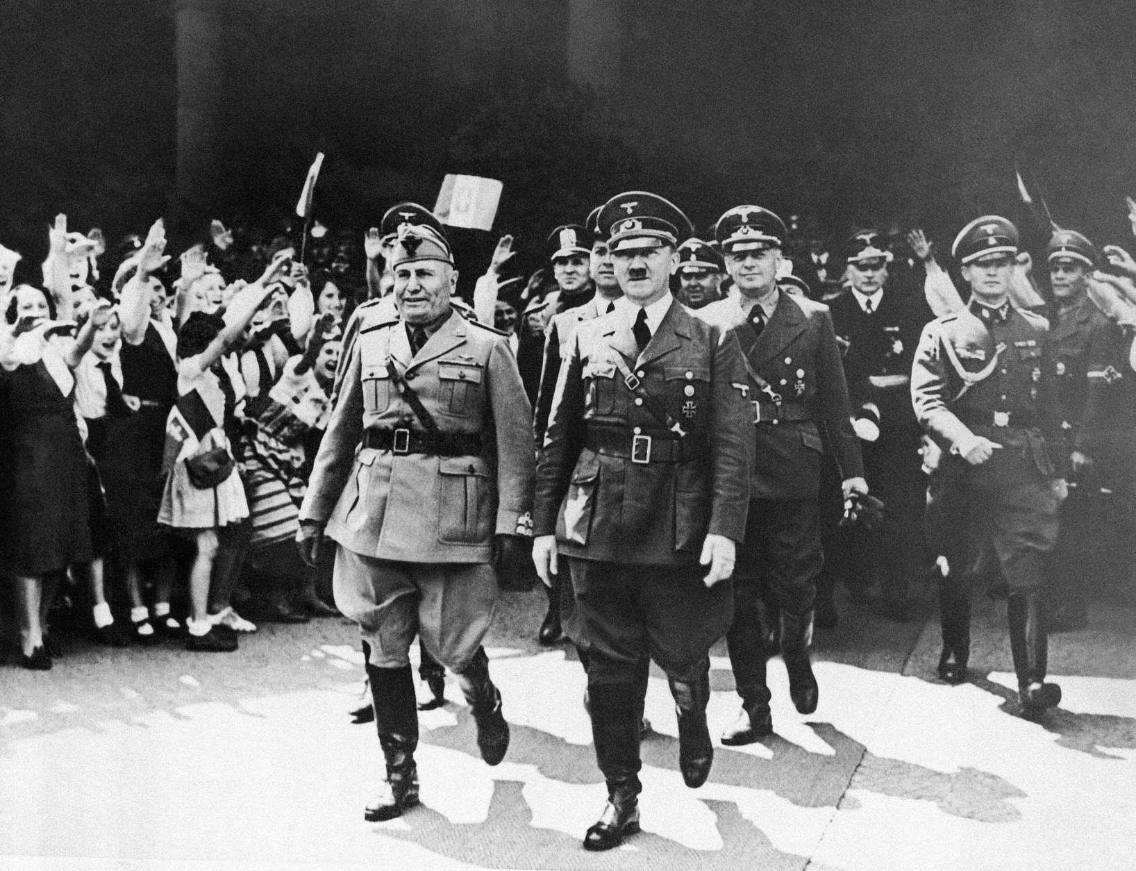 """Benito Mussolini, left, and Adolf Hitler move along in step, smilingly accepting the plaudits of Munich residents when they met to discuss armistice terms for beaten France on June 18, 1940. Joyous expressions on faces of women and girls at left as they raise their arms to """"Heil"""" the axis leaders. (AP Photo)"""