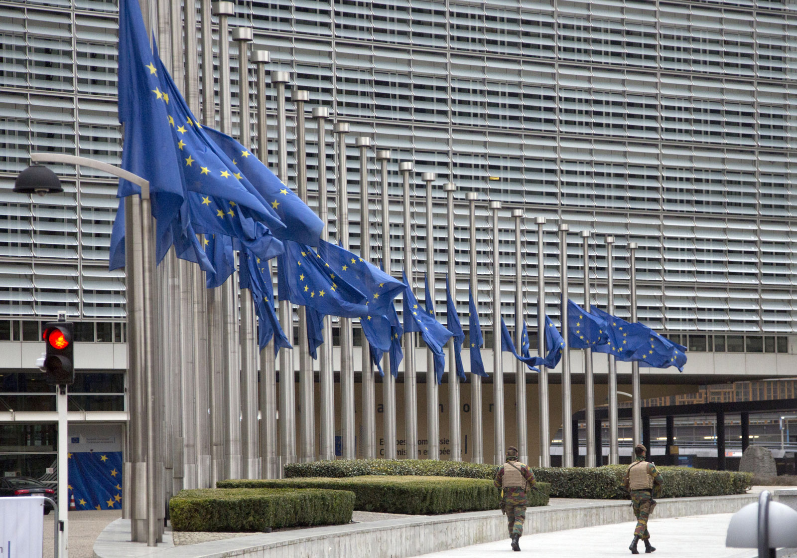 Two soldiers from the Belgian Army patrol outside EU headquarters as EU flags fly at half mast after an explosion in Brussels on Tuesday, March 22, 2016. Explosions, at least one likely caused by a suicide bomber, rocked the Brussels airport and subway system Tuesday, prompting a lockdown of the Belgian capital and heightened security across Europe. At least 26 people were reported dead. (AP Photo/Virginia Mayo)