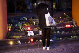 A woman lays flowers in front of the Belgium Embassy in Berlin, Germany, Tuesday, March 22, 2016, after Tuesday's terrorist attacks in Brussels. (AP Photo/Markus Schreiber)