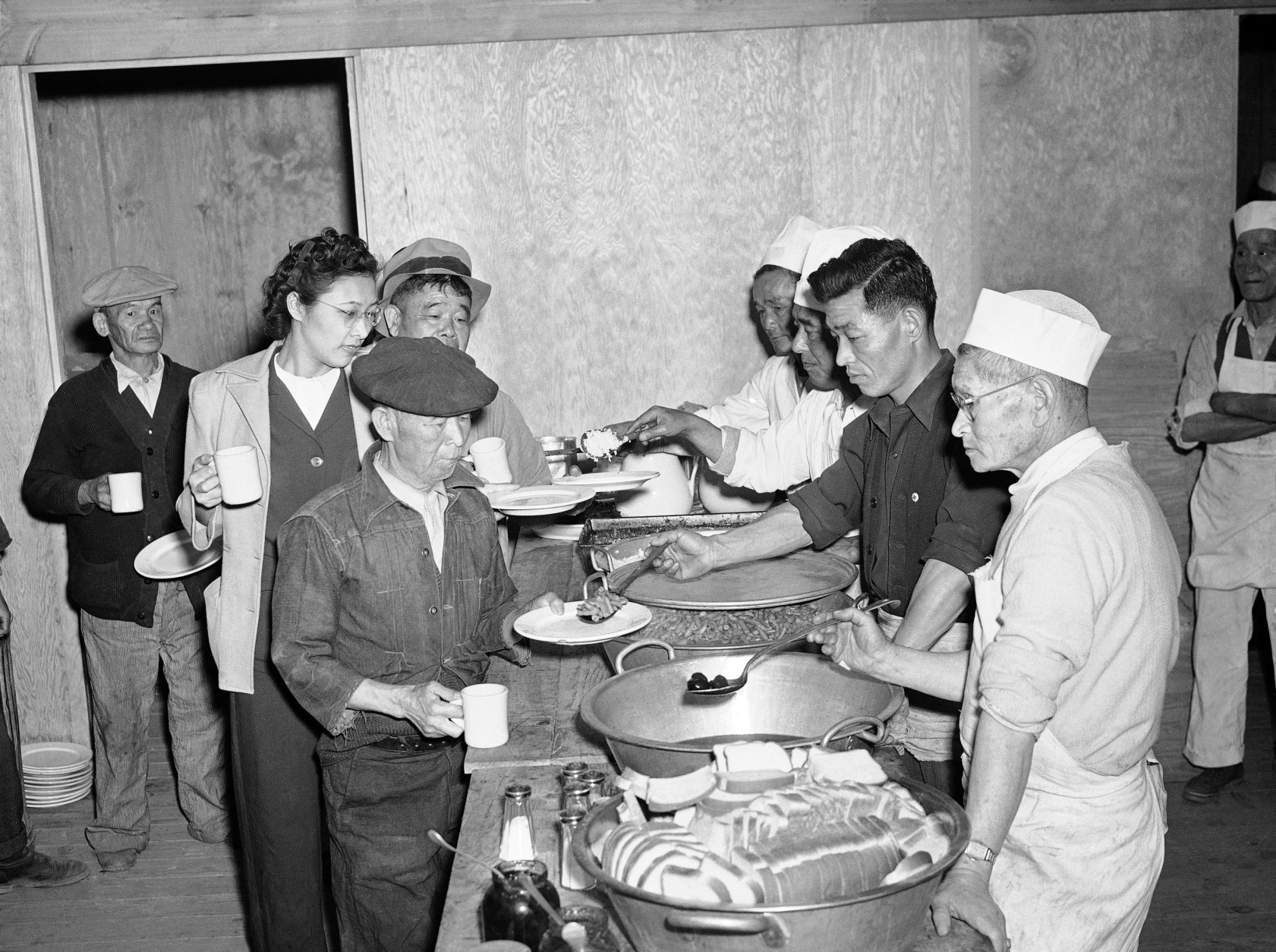 Japanese removed from their Los Angeles homes line up at the government's alien camp at Manzanar, Calif. March 23, 1942 for their first meal after arrival at the camp. Rice, Beans, Prunes bread were included in the menu. (AP Photo)