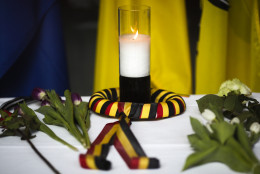 After  attacks in Brussels, a candle wrapped in a ribbon in the colors of the Belgium national flag and flowers are  placed on a table inside the Belgium Embassy in Berlin, Germany, Tuesday, March 22, 2016. (AP Photo/Markus Schreiber)