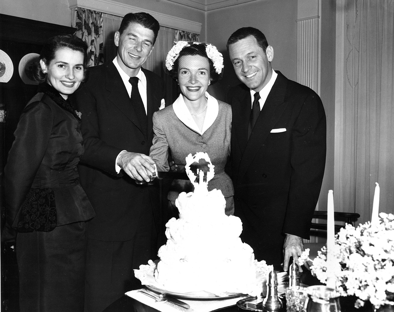 Actor Ronald Reagan and his bride, actress Nancy Davis, cut their wedding cake after their marriage at the non-sectarian Little Brown Church of the Valley in North Hollywood, Ca., March 4, 1952.  With them are actress Brenda Marshall, left, and her husband, actor William Holden.  (AP Photo)