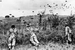The first landed paratroopers of the French-Indochinese Union army have a watchful eye on the descent of their comrades, as Operation Castor gets under way, on November 20, 1953, in the hill tops district northwest of Hanoi . Several paratrooper units are launched in a campaign to strenghten the garrison of Dien Bien Phu. (AP Photo)