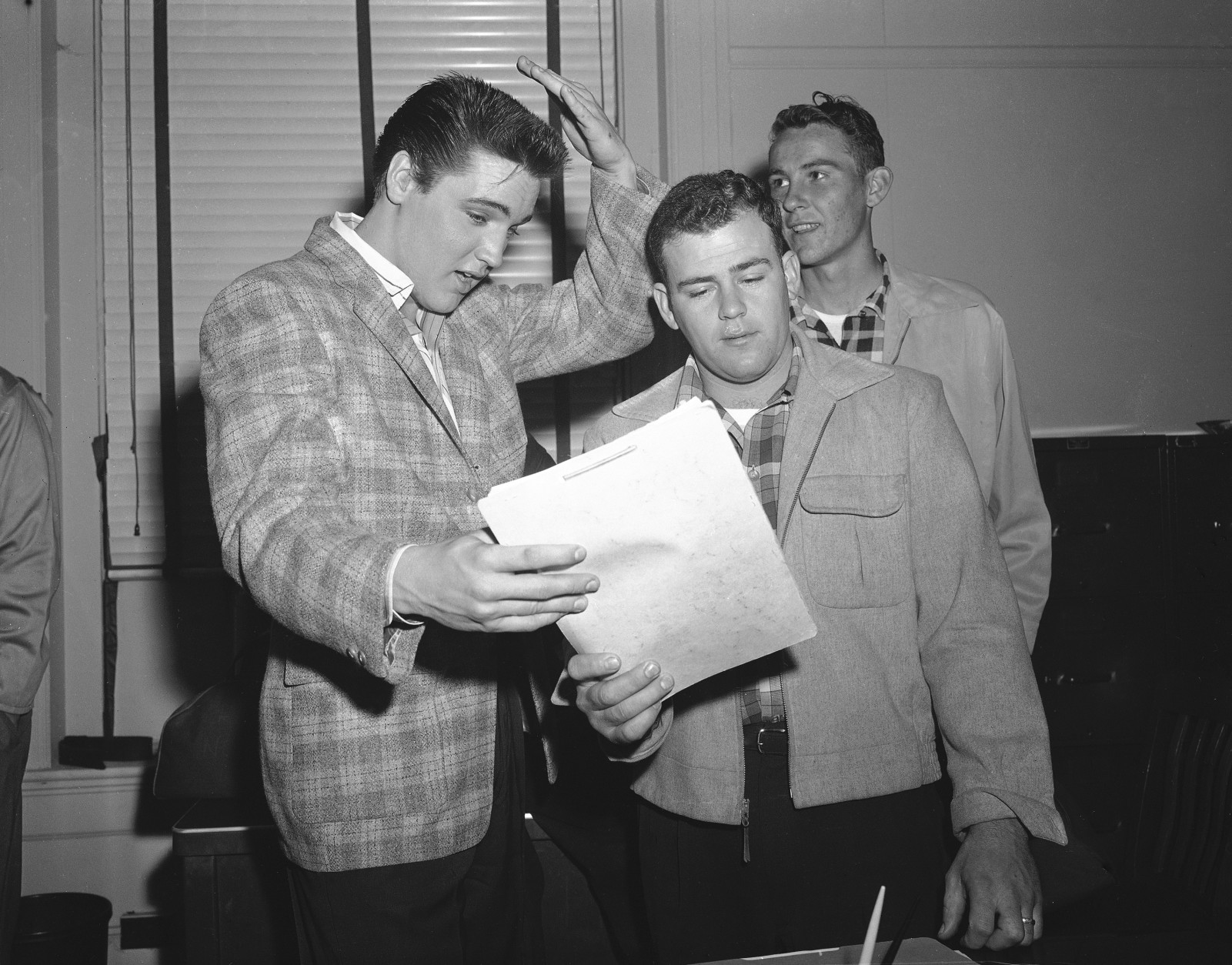 Elvis Presley, left, 23-year-old rock and roll singer, gestures at his short hair as he chats with a former school chum, Farley Gey, 22, who is entering the Army with Elvis, in Memphis, March 24, 1958. Robert Maharrey, 22, another inductee, looks on from the rear. The scene took place at the local draft board headquarters. (AP Photo/Fred J. Griffith)