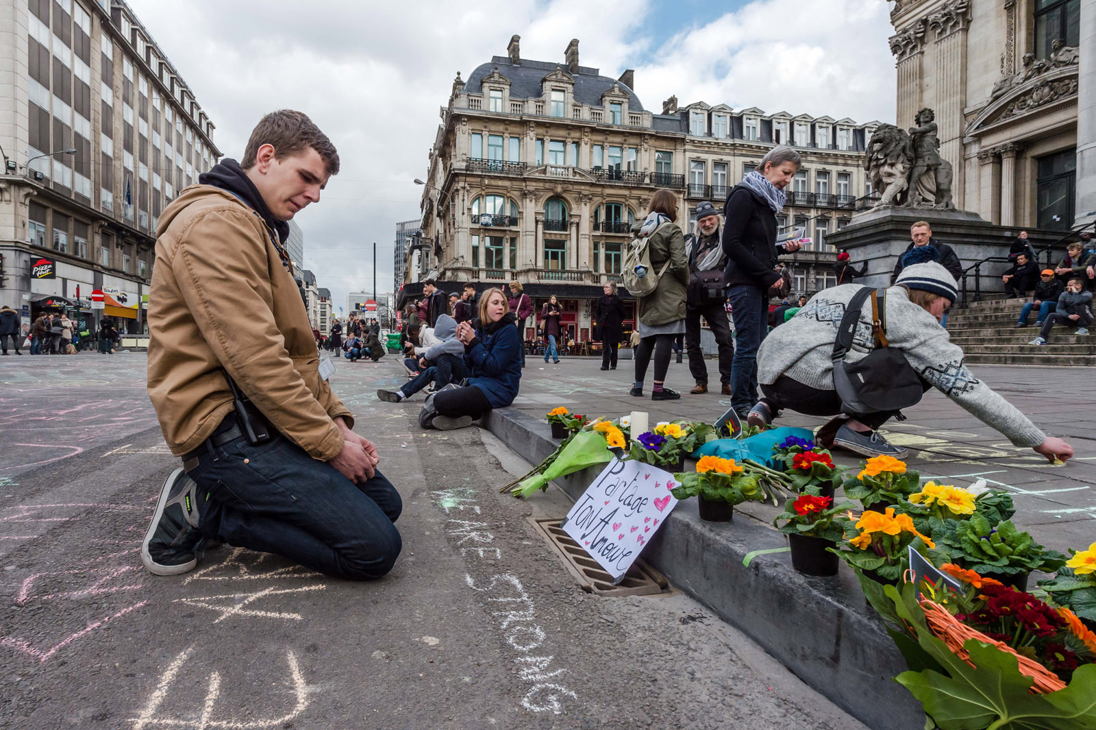 A man looks at flowers and messages outside the stock exchange in Brussels on Tuesday, March 22, 2016. Explosions, at least one likely caused by a suicide bomber, rocked the Brussels airport and subway system Tuesday, prompting a lockdown of the Belgian capital and heightened security across Europe. At least 26 people were reported dead. (AP Photo/Geert Vanden Wijngaert)