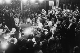 The entire Grand Ole Opry company crowds onstage on March 9, 1963 as Opry Manager Ott Devine (at podium) delivers a message honoring five members killed in accidents last week. It was the same old rollicking show, but onlookers backstage saw through the facade. During Minnie Pearl's (at Devine's left) performance night, she raced offstage at the end of her act with a typical roar of laughter, then burst into tears in the wings. (AP Photo/Brian Calvert)
