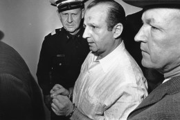 Nightclub owner Jack Ruby is led through the Dallas city jail on his way to his arraignment in Dallas, Tex. on Nov. 24, 1963.  Ruby was charged for the murder of Lee Harvey Oswald, the man accused with assassinating John F. Kennedy.  Others are unidentified.  (AP Photo)