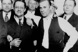 Captured desperado John Dillinger, wearing vest, strikes a jaunty pose with prosecutor Robert Estill in what would become an infamous image at the Crown Point, Ind., jailhouse, Feb. 1934. (AP Photo)