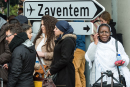 People stand near Brussels airport after being evacuated following  explosions that rocked the facility in Brussels, Belgium, Tuesday March 22, 2016. Authorities locked down the Belgian capital on Tuesday after explosions rocked the Brussels airport and subway system, killing  a number of people and injuring many more. Belgium raised its terror alert to its highest level, diverting arriving planes and trains and ordering people to stay where they were. Airports across Europe tightened security. (AP Photo/Geert Vanden Wijngaert)