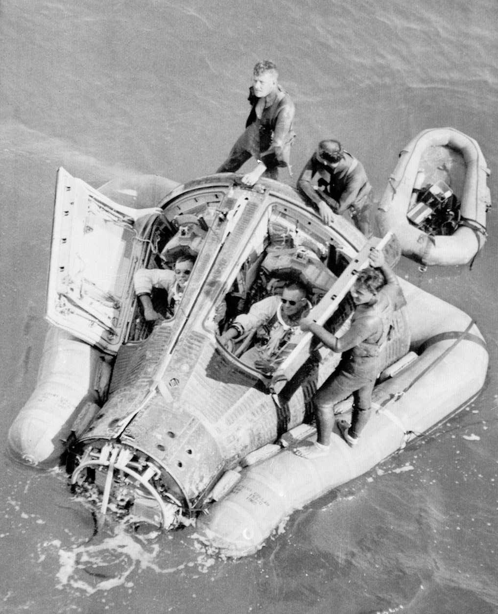 Astronauts David R. Scott, pilot, left, and Neil A. Armstrong, command pilot, sit in their Gemini 8 spacecraft after their emergency landing at 10:23 p.m. in the western Pacific Ocean, March 16, 1966.  Navy divers, who jumped into the ocean to attach flotation collar under the spacecraft, stand outside the capsule awaiting the destroyer USS Mason.  The scheduled three-day mission was terminated following complications.  The mission objective of rendezvous and dock with the Gemini Agena target vehicle (GATV) was accomplished.  (AP Photo/NASA)