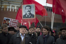 """Russian Communist Party leader and lawmaker Gennady Zyuganov, foreground left, speaks to the media as communist party supporters holds portraits of Soviet dictator Josef Stalin and red flags marking the 61st anniversary of his death in Red Square in Moscow, Russia, Wednesday, March 5, 2014.  Stalin led the Soviet Union from 1924 until his death in 1953. Communists credit him with leading the country to victory in World War II while others condemn the brutal purges that killed millions. The sign at left reads """"without Stalin there could not be Russia."""" (AP Photo/Alexander Zemlianichenko)"""
