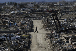 """FILE - In this March 27, 2011 file photo, a man walks through the destroyed neighborhood below Weather Hill in Natori, Japan. The hill was originally built to give fishermen a view of sea conditions but now offers an unforgettable look out over the vastness of the mass destruction left from tsunami caused by the March 11 earthquake. As Japan's """"triple disaster"""" - quake, tsunami and nuclear crisis - unfolded after March 11, 2011, Associated Press journalists fanned out across the northern region of Tohoku to report and record what had happened in pictures, stories and video footage. (AP Photo/Wally Santana, File)"""