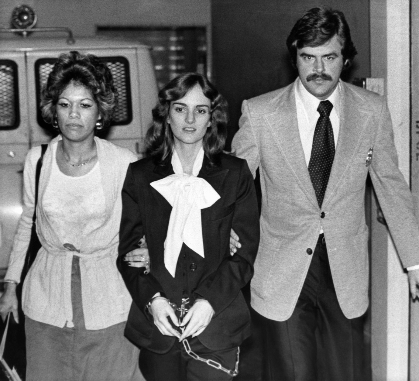 U.S. marshals escort Patricia Hearst from San Francisco's Federal Building in San Francisco, Feb. 3, 1976, where jury selection continued in her bank robbery trial. The jury is expected to be seated on Tuesday, raising the possibility the first testimony would be hears on Wednesday – the second anniversary of Miss Hearst's kidnapping by the Symbionese Liberation Army. At left is Marshal Janey Jimenez, and at right is Marshal Mike Tarr. (AP Photo)
