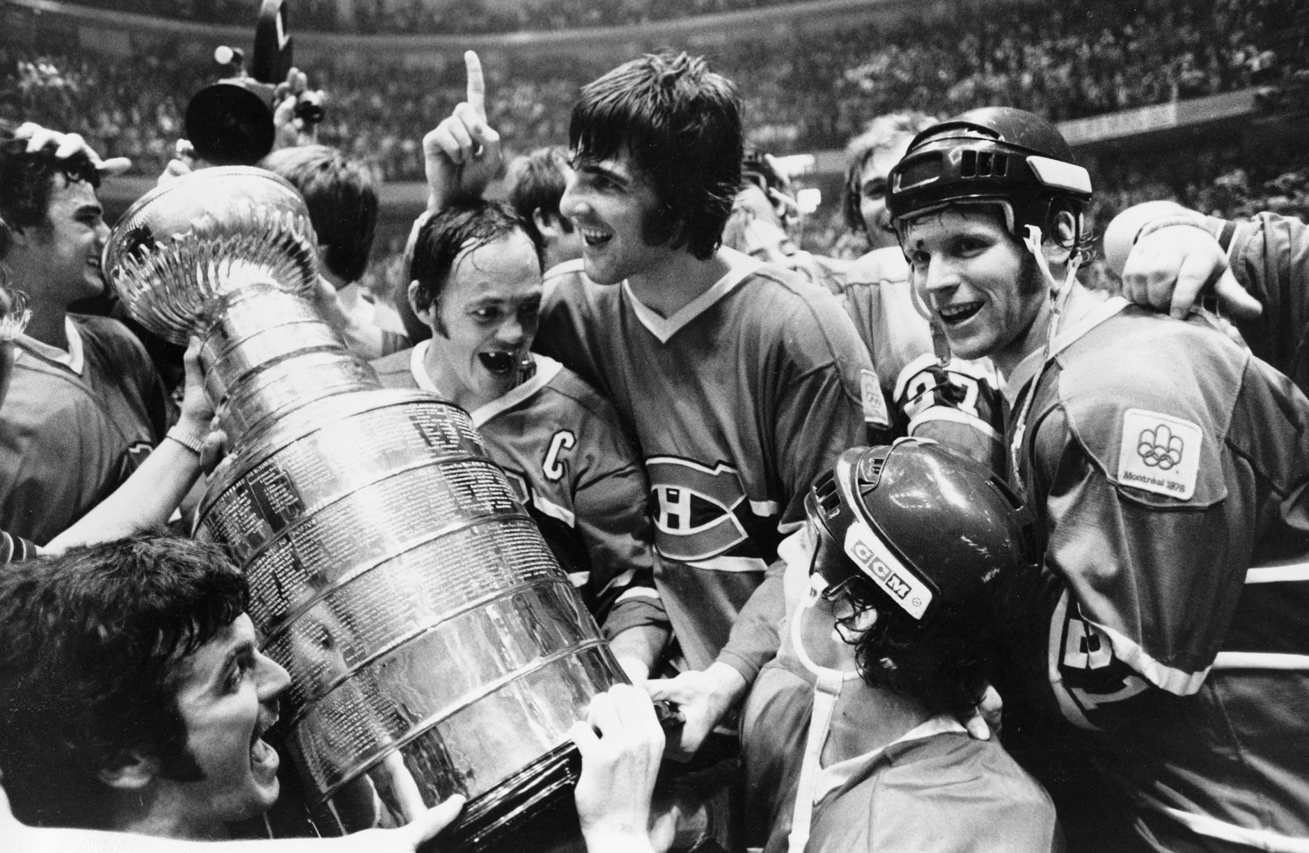 Yvan Cournoyer, captain of the Montreal Canadiens, holds the Stanley Cup as he is surrounded by teammates in Philadelphia, Pa., Sunday night, May 16, 1976.  Montreal beat the Philadelphia Flyers to take the final series of the cup.  (AP Photo)