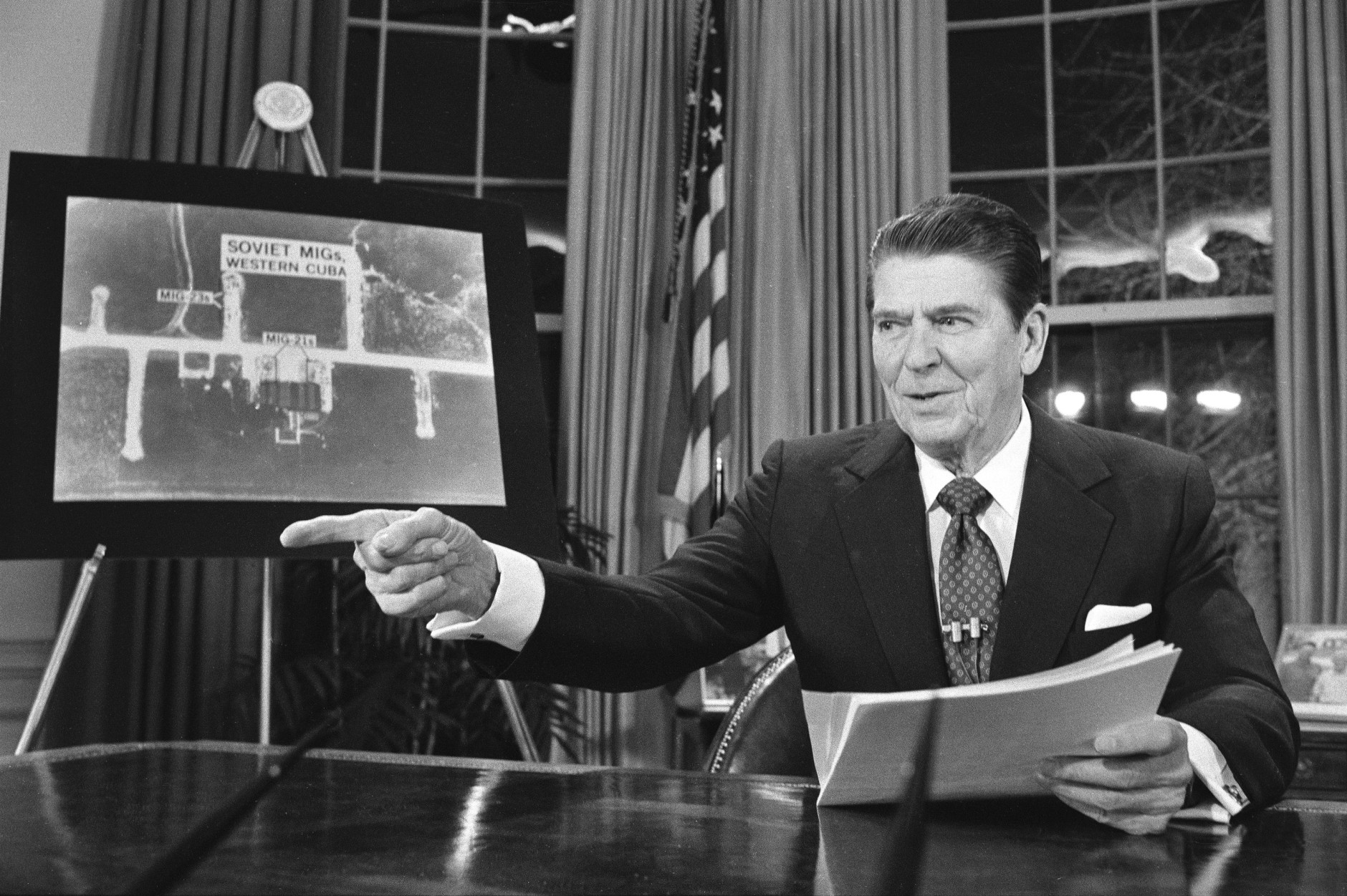 President Reagan points as he addresses the nation on television March 23, 1983, from Washington in support of his proposed defense budget.  At left is a picture of Soviet Migs in western Cuba according to the White House.  The House voted earlier to cut the defense budget in favor of social programs.  (AP Photo/Dennis Cook)