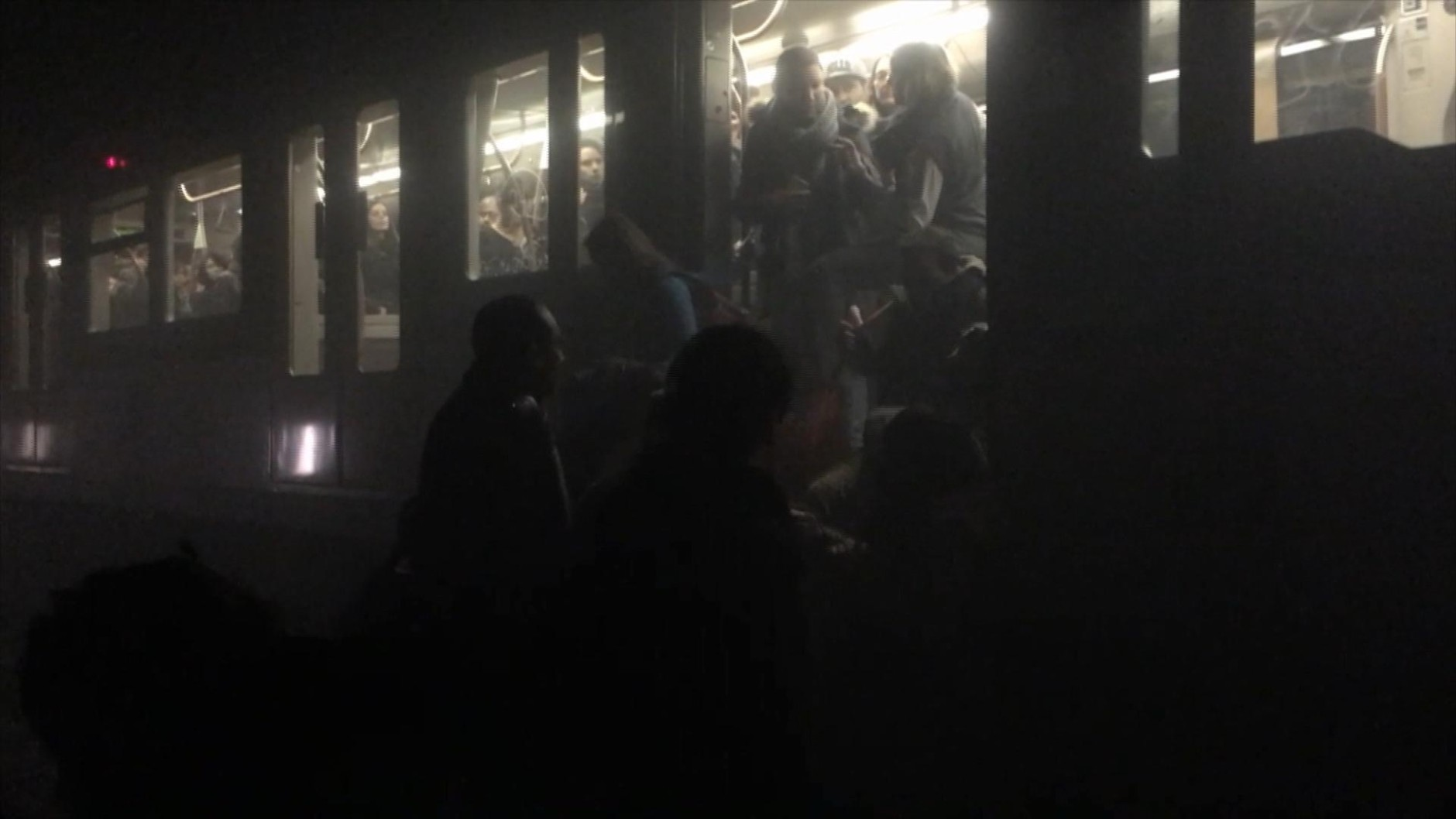 In this photo provided by Evan Lamos passengers clamber from a metro carriage after explosions in Brussels Tuesday, March 22, 2016. Authorities locked down the Belgian capital on Tuesday after explosions rocked the Brussels airport and subway system, killing  a number of people and injuring many more. Belgium raised its terror alert to its highest level, diverting arriving planes and trains and ordering people to stay where they were. Airports across Europe tightened security.  (Evan Lamos via AP)