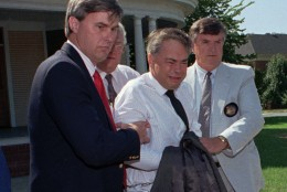 U.S. marshals escort former PTL leader Jim Bakker, center, from his attorney's office to a waiting car Thursday afternoon Aug. 31, 1989 in Charlotte, N.C.   Bakker, who did not appear in court Thursday, was taken under order to the State Correctional Institute at Butner, N.C., for psychiatric evaluation.  (AP Photo/Chuck Burton)